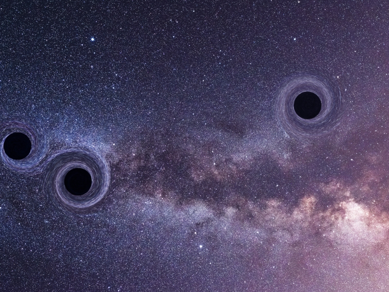 A photo illustration of three black holes on a starry sky background.